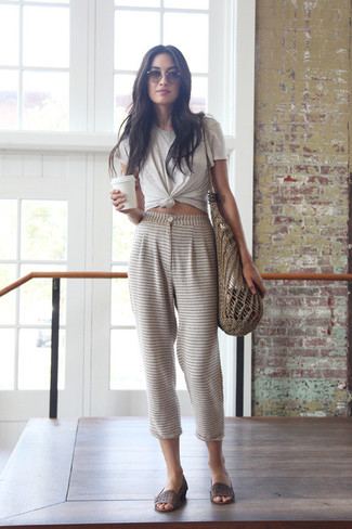 Opt for comfort in a camel crew-neck t-shirt and tan striped casual pants. A cool pair of dark brown leather heeled sandals is an easy way to upgrade your look.