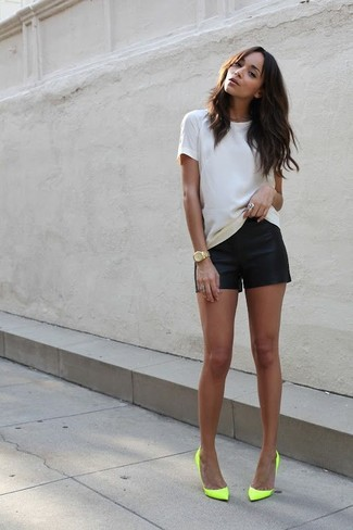This pairing of a white crew-neck tee and black leather shorts is super versatile and really up for any sort of adventure you may find yourself on. Let's make a bit more effort now and choose a pair of neon yellow leather pumps. Loving how great this combination is come summertime.