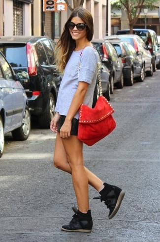 Consider wearing a grey crew-neck t-shirt and black leather shorts for both chic and easy-to-wear look. Black suede wedge sneakers are a great choice to complete the look.