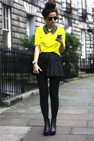 Make a green-yellow t-shirt and a black leather skater skirt your outfit choice for a lazy Sunday brunch. For footwear go down the classic route with black leather booties.