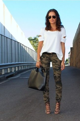 Stand out among other stylish civilians in a white cutout crew-neck tee and dark green skinny jeans. Black leather gladiator sandals are the right shoes here to get you noticed.