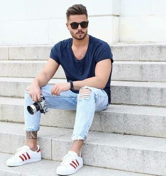 How to Wear Light Blue Ripped Skinny Jeans For Men: This laid-back combo of a navy crew-neck t-shirt and light blue ripped skinny jeans is a winning option when you need to look dapper but have zero time to plan out an ensemble. Play up the formality of this outfit a bit by finishing with a pair of white and red leather low top sneakers.
