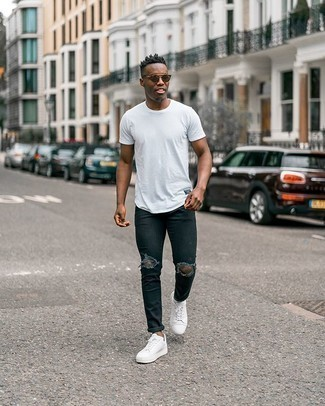 Men's Outfits 2020: For something more on the casually edgy side, try this pairing of a white crew-neck t-shirt and black ripped skinny jeans. Choose a pair of white canvas low top sneakers to effortlessly amp up the wow factor of this getup.