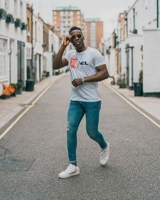 Men's Outfits 2020: This relaxed casual pairing of a white print crew-neck t-shirt and blue ripped skinny jeans is a surefire option when you need to look nice but have no time. For something more on the classy side to round off your look, complement this outfit with a pair of white canvas low top sneakers.