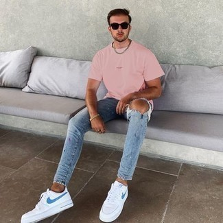 Light Blue Ripped Skinny Jeans Outfits For Men: If you're on the lookout for a relaxed and at the same time dapper getup, consider pairing a pink crew-neck t-shirt with light blue ripped skinny jeans. Finishing with a pair of white and blue canvas low top sneakers is an easy way to introduce a little classiness to your getup.
