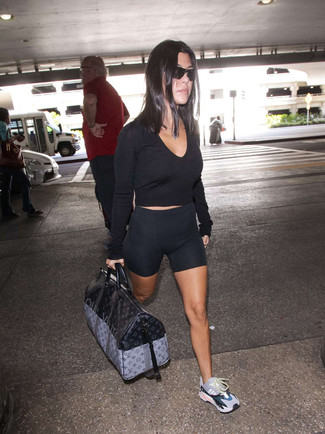 How to wear: black cropped sweater, black bike shorts, multi colored athletic shoes, black print leather duffle bag