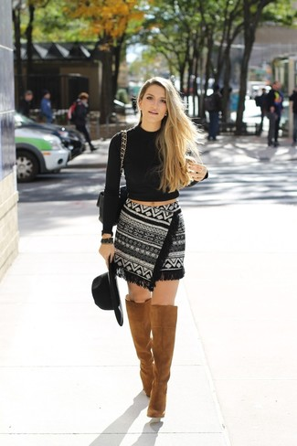 A black cropped sweater and a black and white geo mini skirt are a great outfit formula to have in your arsenal. A cool pair of khaki suede knee high boots is an easy way to upgrade your look.