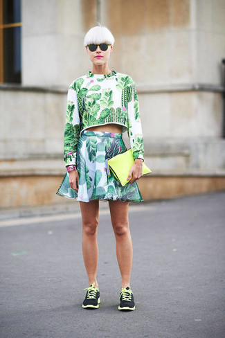 Choose a green floral cropped sweater and a green floral skater skirt for a trendy and easy going look. Make black athletic shoes your footwear choice for a more relaxed feel.