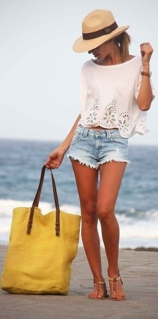 Marry a white eyelet cropped top with light blue denim shorts to achieve a chic look. A pair of brown leather thong sandals brings the dressed-down touch to the ensemble.