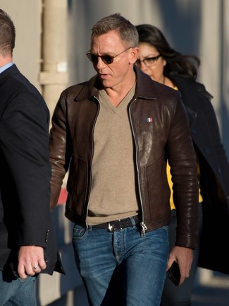 How to wear: dark brown leather bomber jacket, tan v-neck sweater, navy jeans, black woven leather belt