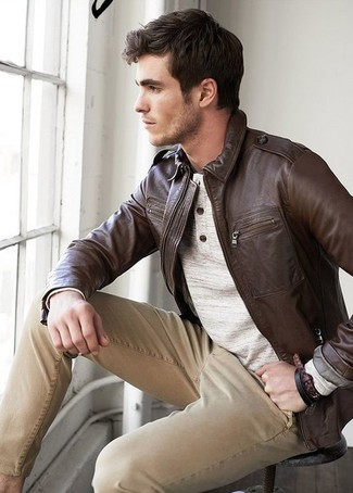 How to wear: dark brown leather bomber jacket, beige henley sweater, khaki chinos