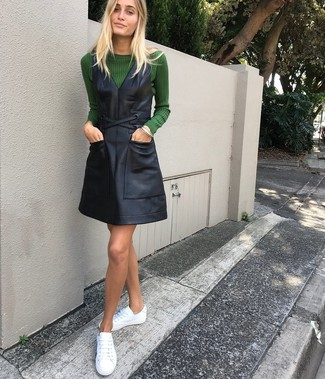 How to wear: dark green crew-neck sweater, black leather overall dress, white leather low top sneakers