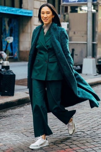 How to Wear a Suit For Women: Marry a dark green fur coat with a suit for a neat polished outfit. Complete your look with a pair of white leather low top sneakers to instantly bump up the fashion factor of this outfit.