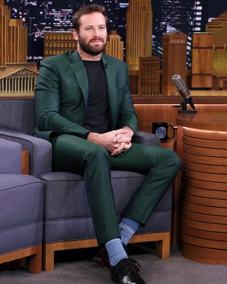 How to wear: dark green suit, black crew-neck sweater, black leather oxford shoes, blue socks