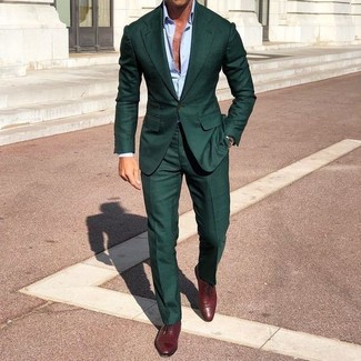 How to Wear a Dark Green Suit: A dark green suit and a light blue dress shirt are absolute essentials if you're picking out a classic wardrobe that matches up to the highest men's fashion standards. Burgundy leather oxford shoes are the perfect complement to this look.