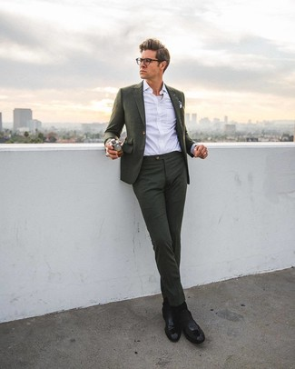 How to Wear a Dark Green Suit: Go for a dark green suit and a white dress shirt if you're going for a neat, smart ensemble. Add a laid-back vibe to by slipping into a pair of black leather chelsea boots.
