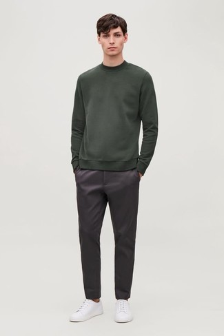 Dark Green Sweatshirt Outfits For Men: This combo of a dark green sweatshirt and dark purple chinos is proof that a safe off-duty getup doesn't have to be boring. The whole look comes together wonderfully when you add a pair of white canvas low top sneakers to the mix.