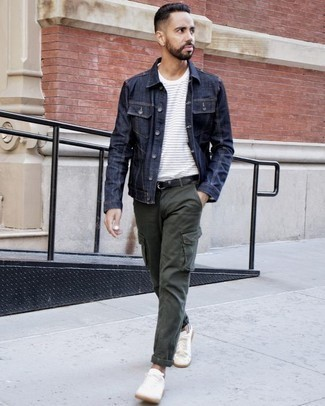 How to Wear a Navy Denim Jacket For Men: Seriously stylish yet comfortable, this ensemble is assembled from a navy denim jacket and dark green cargo pants. A pair of white canvas low top sneakers will be the ideal accompaniment to this ensemble.