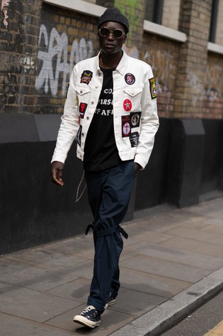 How to wear: white embroidered denim jacket, black and white print crew-neck t-shirt, navy chinos, black canvas low top sneakers