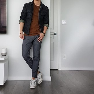 Charcoal Jeans Outfits For Men: For a relaxed casual getup with a modern spin, try pairing a black denim jacket with charcoal jeans. Let your sartorial savvy truly shine by finishing this look with white leather low top sneakers.