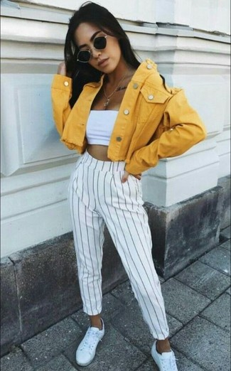 How to wear: yellow denim jacket, white cropped top, white and black vertical striped dress pants, white leather low top sneakers