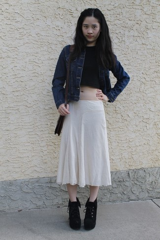 A navy denim jacket and a beige pleated midi skirt are perfect for both running errands and a night out. Elevate this ensemble with black suede lace-up ankle boots.