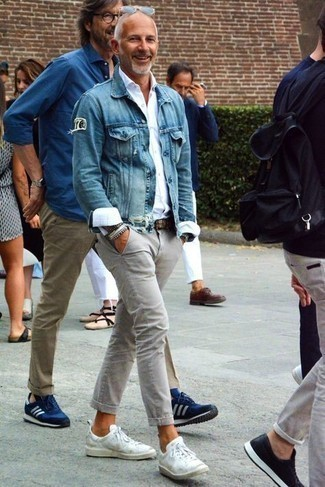 Grey Chinos Outfits: Go for a simple yet neat and relaxed option marrying a blue denim jacket and grey chinos. A nice pair of white leather low top sneakers is an effortless way to add a dash of stylish nonchalance to this outfit.