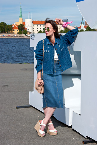 Make a blue denim jacket and a blue denim midi skirt your outfit choice for a comfortable outfit that's also put together nicely. A pair of white leather wedge sandals fits right in here. Mastering transitional fashion is easy with style inspiration like this.