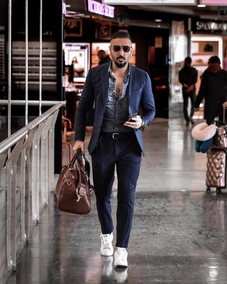 How to wear: blue denim jacket, navy suit, white leather low top sneakers, brown leather holdall