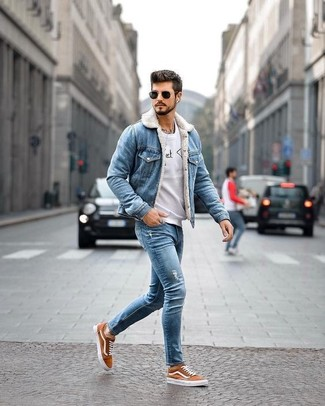 How to wear: blue denim jacket, grey print sweatshirt, blue ripped skinny jeans, tobacco canvas low top sneakers