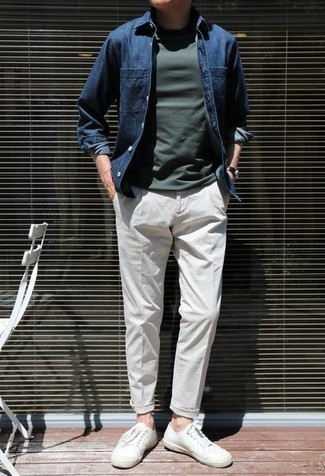 Blue Denim Shirt Outfits For Men: This casual pairing of a blue denim shirt and white chinos is very easy to throw together in next to no time, helping you look on-trend and prepared for anything without spending too much time searching through your closet. Let your outfit coordination savvy truly shine by finishing off this getup with a pair of white canvas low top sneakers.
