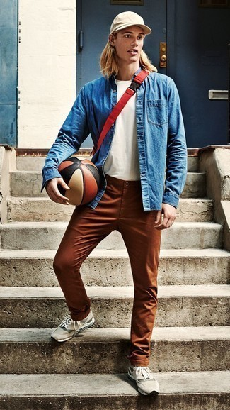 Blue Denim Shirt Outfits For Men: If you prefer laid-back looks, why not take this combo of a blue denim shirt and tobacco chinos for a spin? For something more on the relaxed side to finish your outfit, introduce a pair of beige athletic shoes to the mix.