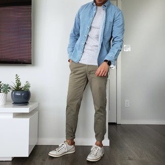 Men's Outfits 2021: For comfort without the need to sacrifice on good style, we love this combination of a light blue denim shirt and olive chinos. Introduce a pair of white leather low top sneakers to the equation and off you go looking killer.