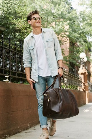 Dark Brown Leather Holdall Outfits For Men: This pairing of a light blue denim shirt and a dark brown leather holdall is hard proof that a straightforward casual look can still look really sharp. You can get a little creative when it comes to shoes and complete your look with a pair of beige suede desert boots.