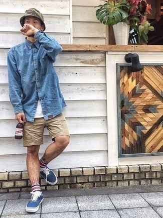 Men's Outfits 2021: This pairing of a blue denim shirt and tan shorts is super stylish and creates instant appeal. Now all you need is a nice pair of navy and white canvas low top sneakers.