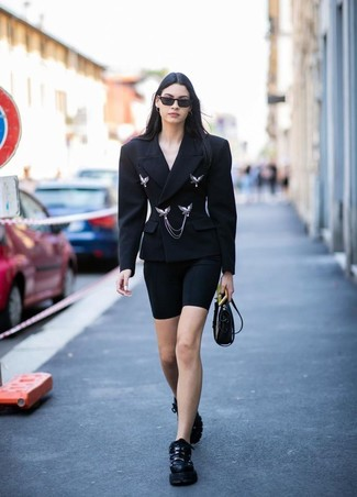 How to wear: black double breasted blazer, black bike shorts, black athletic shoes, black leather crossbody bag