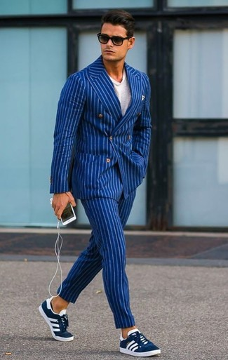 How to wear: blue vertical striped double breasted blazer, white crew-neck t-shirt, blue vertical striped dress pants, navy suede low top sneakers