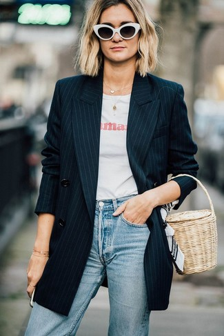 How to wear: black vertical striped double breasted blazer, white and red print crew-neck t-shirt, light blue jeans, beige straw handbag