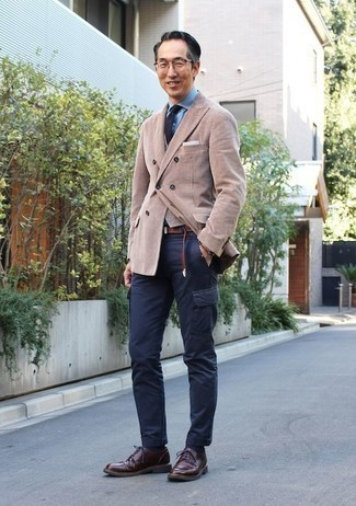 How to Wear a Tan Double Breasted Blazer For Men: A tan double breasted blazer and navy cargo pants are absolute staples if you're putting together a semi-casual closet that matches up to the highest fashion standards. Let's make a bit more effort now and introduce burgundy leather derby shoes to the mix.