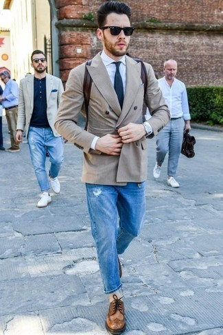 How to Wear a Beige Double Breasted Blazer For Men: If you're looking for a laid-back and at the same time sharp look, team a beige double breasted blazer with blue ripped jeans. Kick up the wow factor of this look by finishing off with brown leather brogues.