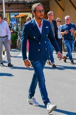 How to Wear a Navy Double Breasted Blazer For Men: This smart combination of a navy double breasted blazer and navy jeans can take on different nuances according to the way you style it out. Finishing with white leather low top sneakers is the simplest way to introduce a bit more edginess to your ensemble.