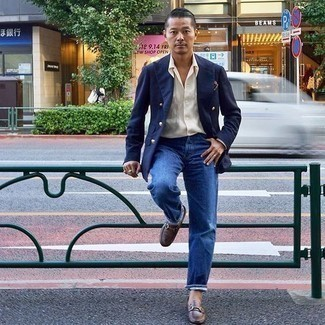 How to Wear a Navy Double Breasted Blazer For Men: A navy double breasted blazer and blue jeans are the ideal way to infuse some manly sophistication into your casual styling arsenal. Want to go all out on the shoe front? Introduce brown leather loafers to the equation.