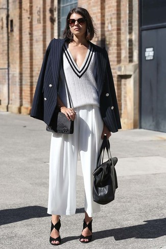 Women's Outfits 2020: A black vertical striped double breasted blazer and white culottes worn together are such a dreamy look for girls who love relaxed outfits. A pair of black suede heeled sandals effortlesslly steps up the oomph factor of any getup.