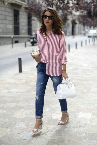 Master the effortlessly chic look in a white and red vertical striped dress shirt and blue ripped boyfriend jeans. Dress up this look with silver leather heeled sandals.