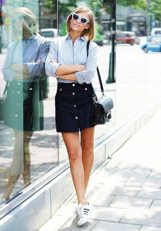 Master the effortlessly chic look in a baby blue vertical striped dress shirt and a navy button skirt. Dress down your look with white leather low top sneakers.