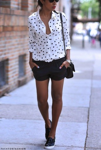 Let everyone know that you know a thing or two about style in a white and black polka dot button-front shirt and black shorts. A pair of black leather slip-on sneakers will be a stylish addition to your outfit.