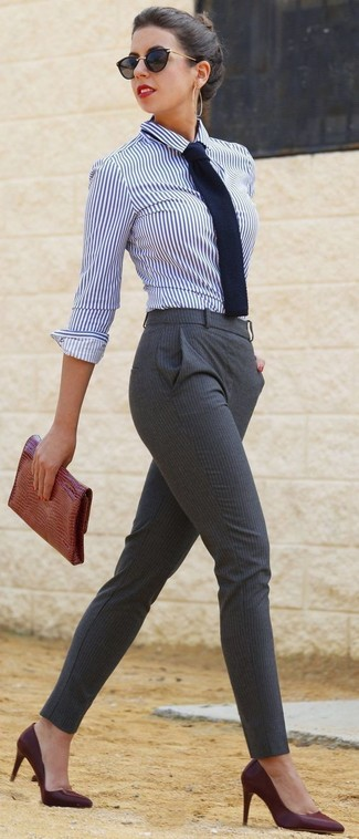 This combination of a white and navy vertical striped classic shirt and grey striped skinny pants spells comfort and style. A pair of oxblood leather pumps will integrate smoothly within a variety of combinations. Rest assured, this ensemble will keep you comfy as well as looking on-trend in this in-between weather.