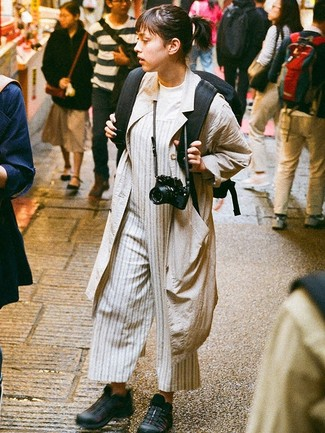 How to wear: beige duster coat, white crew-neck t-shirt, grey vertical striped jumpsuit, black athletic shoes