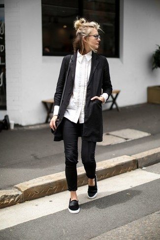 Team a black duster coat with black leggings for a casual get-up. This outfit is complemented perfectly with black suede slip-on sneakers.