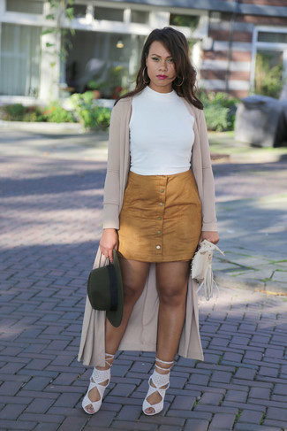 Pair a beige duster coat with a button skirt to effortlessly deal with whatever this day throws at you. Let's make a bit more effort now and choose a pair of white suede heeled sandals. This outfit is absolutely great to welcome spring.